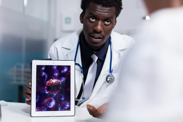 Doutor da etnia afro-americana segurando um tablet digital