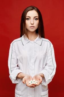 Doutor da jovem mulher no revestimento médico branco que guarda comprimidos em suas palmas abertas, espaço da cópia, isolado. conceito de saúde