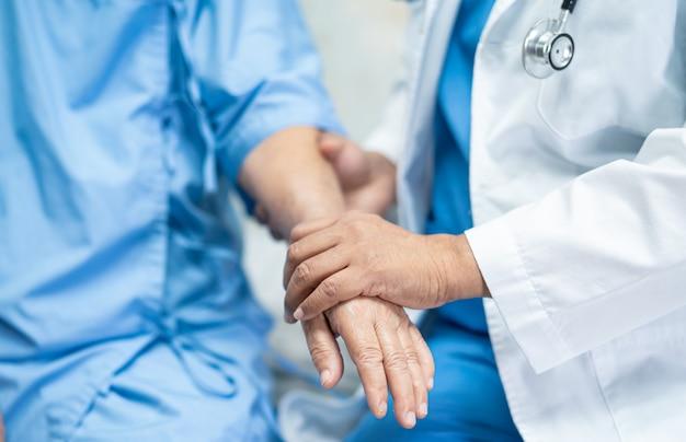 Doutor, de mãos dadas paciente asiático sênior mulher com amor.