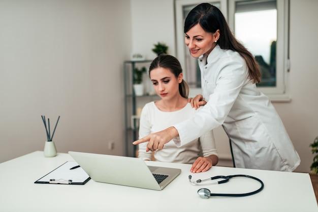 Doutor de sorriso que mostra algo no portátil a seu paciente.