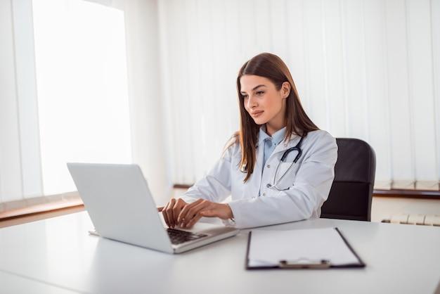 Doutor digitação relatório no laptop.