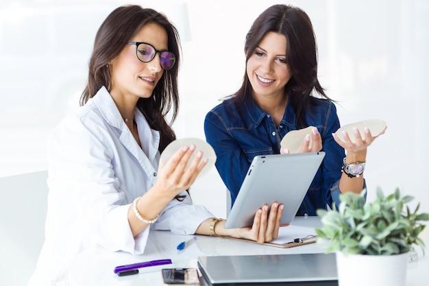 Doutor e seu paciente escolhendo prótese mamária no escritório.