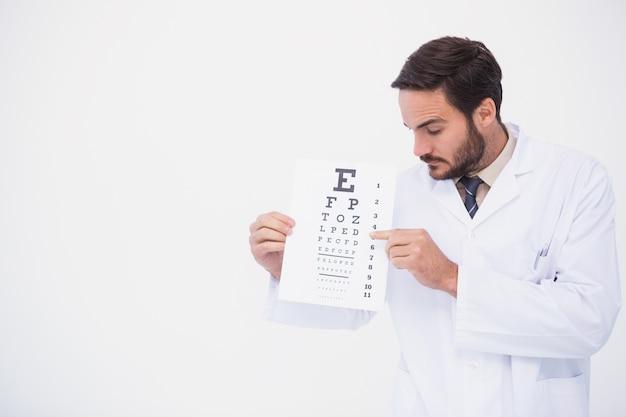 Doutor em bata de laboratório mostrando teste de olho
