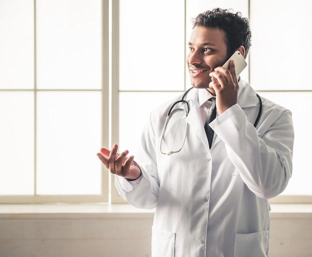 Doutor em jaleco branco está falando no telefone celular.