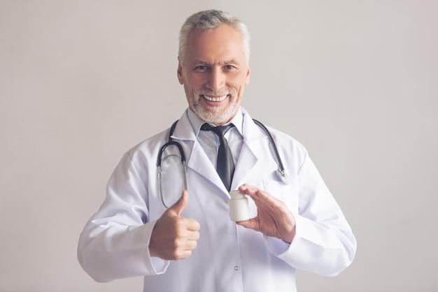 Doutor em jaleco branco está segurando um frasco de remédio.