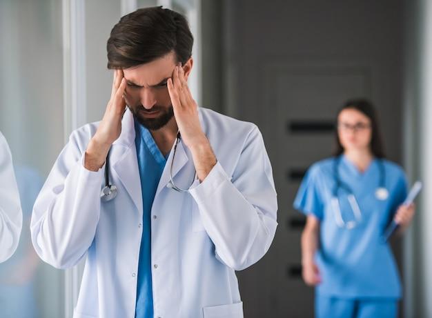 Doutor em jaleco branco está tocando suas têmporas.