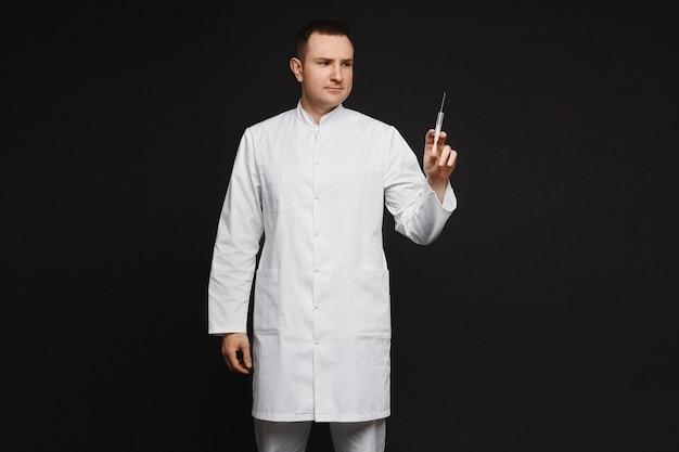 Doutor em jaleco branco segurando uma seringa médica para injeção, isolada no fundo preto.