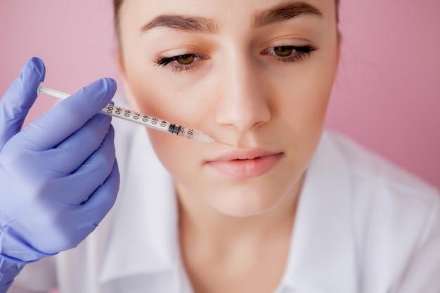 Doutor em luvas dando injeções de botox mulher nos lábios, na parede rosa