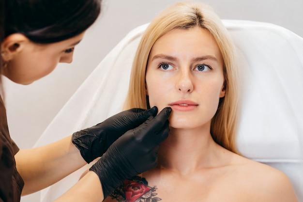 Doutor em luvas dando injeções de mulher nos lábios