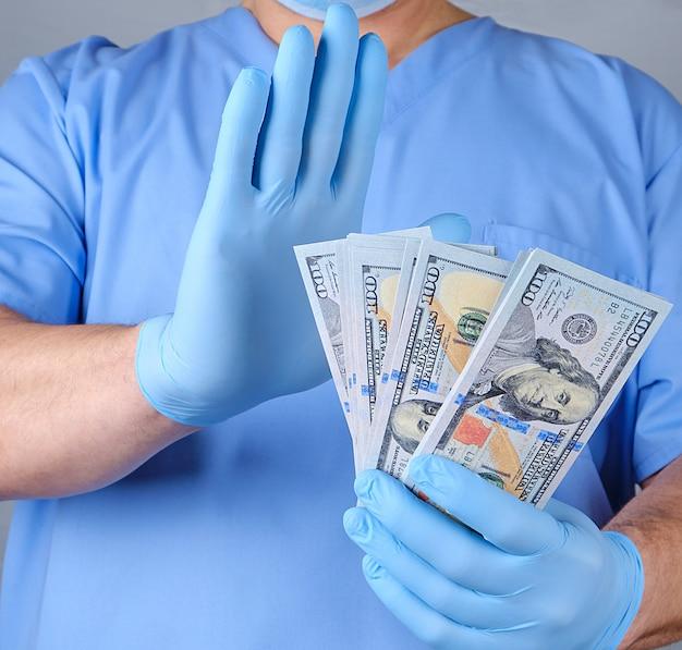 Doutor em luvas de uniforme azul e datex detém um monte de papel-moeda