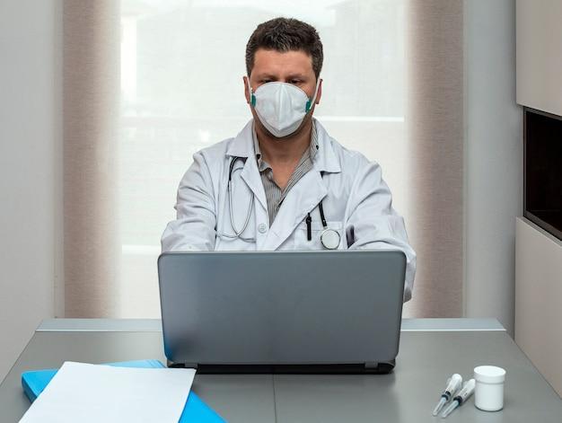 Doutor em máscara médica protetora trabalhando no laptop.