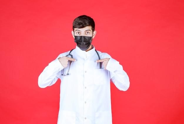 Doutor em máscara preta com estetoscópio no pescoço.