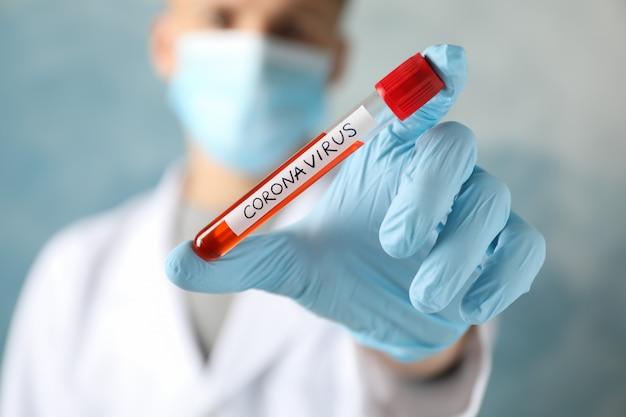 Doutor em máscara protetora realiza exame de sangue positivo no coronavírus. cuidados de saúde e conceito médico
