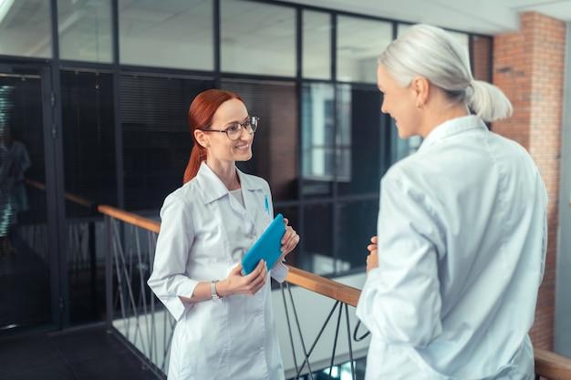 Doutor em óculos. jovem médica sorridente ruiva em pé no corredor, segurando um tablet e conversando com sua colega