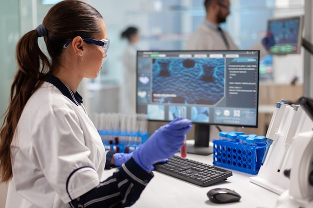 Doutor em química analisando amostra de sangue e digitando no computador enquanto um colega de trabalho abre a porta usando o computador digital. cientista de saúde trabalhando em um laboratório moderno, usando tecnologia moderna.