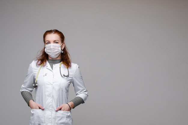 Doutor em respirador e jaleco branco. médico profissional com cabelo vermelho