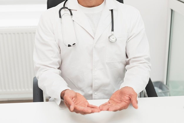 Doutor em roupão branco, mostrando as mãos