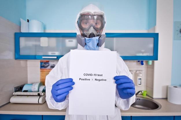 Doutor em traje de proteção uniforme e máscara detém os resultados dos testes de coronovírus.