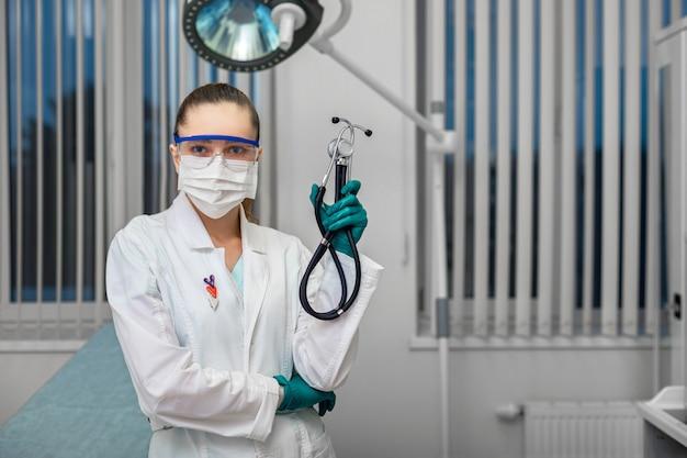 Doutor em um jaleco branco em uma máscara com óculos e luvas segurando um estetoscópio no contexto de um quarto de hospital.