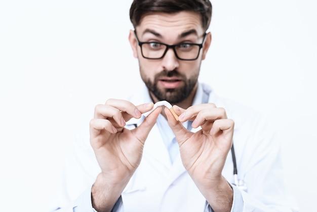 Doutor em um jaleco branco manchas um cigarro.