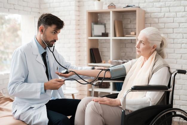 Doutor em um jaleco branco mede a pressão da mulher.