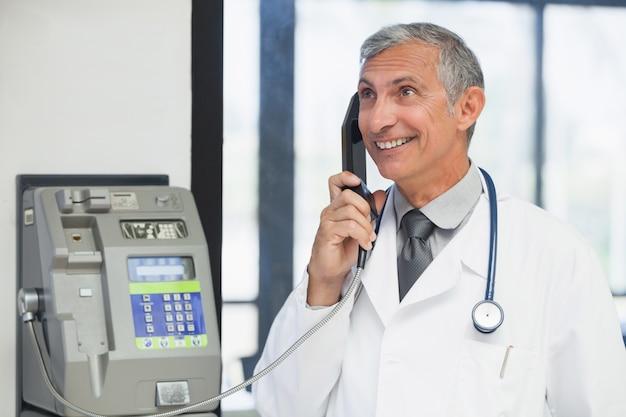 Doutor em um telefone público e sorrindo no hospital