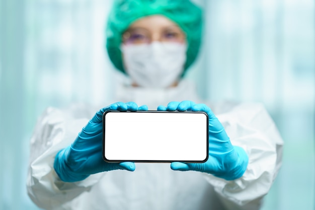 Doutor em um traje de proteção segurando um smartphone