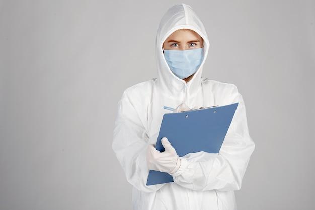 Doutor em uma máscara médica. tema coronavirus. isolado sobre a parede branca. mulher em uma roupa de proteção.