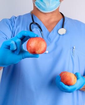 Doutor em uniforme azul e luvas de látex estéreis detém maçãs vermelhas maduras