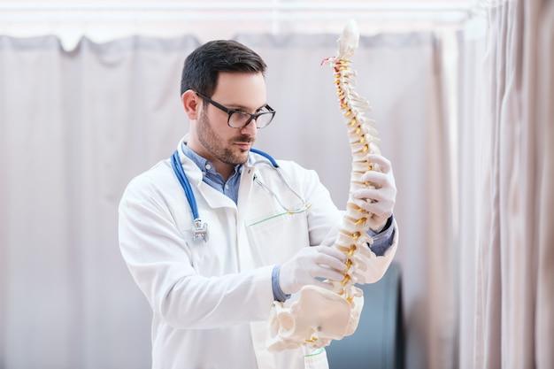Doutor em uniforme branco, segurando o modelo da espinha.
