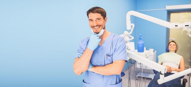Doutor em uniforme médico azul no consultório odontológico e paciente na cadeira odontológica