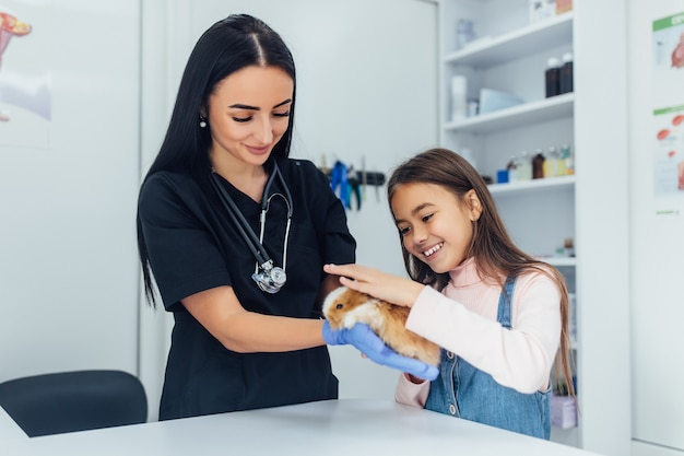 Doutor em uniforme preto, filha pequena com seu animal de estimação chinchila no veterinário. Foto gratuita