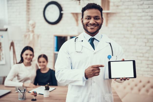 Doutor está posando com tablet com mãe e filha.