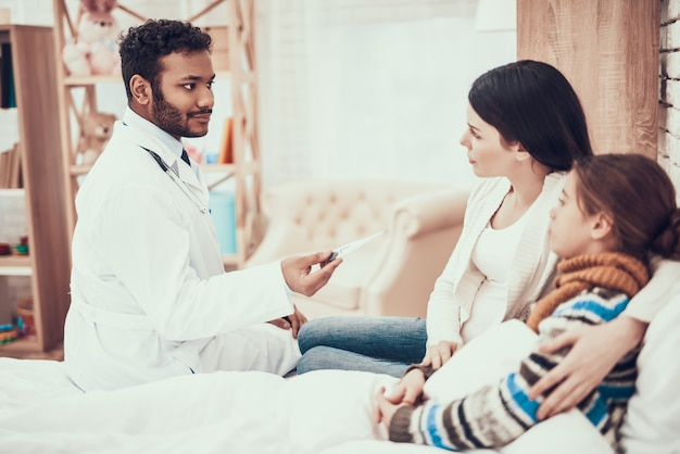 Doutor está tomando a temperatura da menina com a mãe grávida.