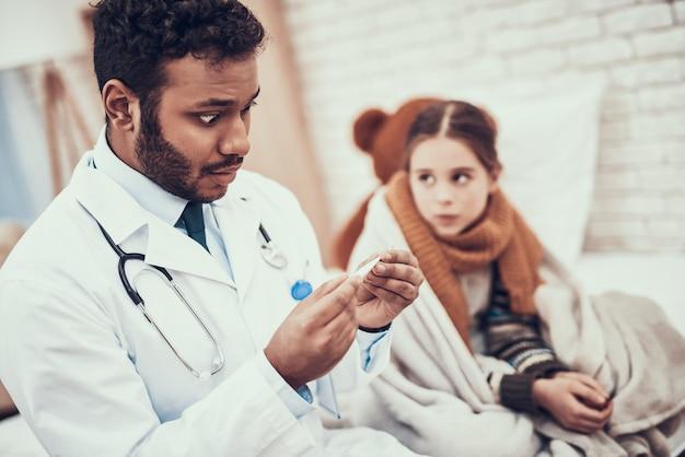 Doutor está tomando a temperatura da menina com o frio.