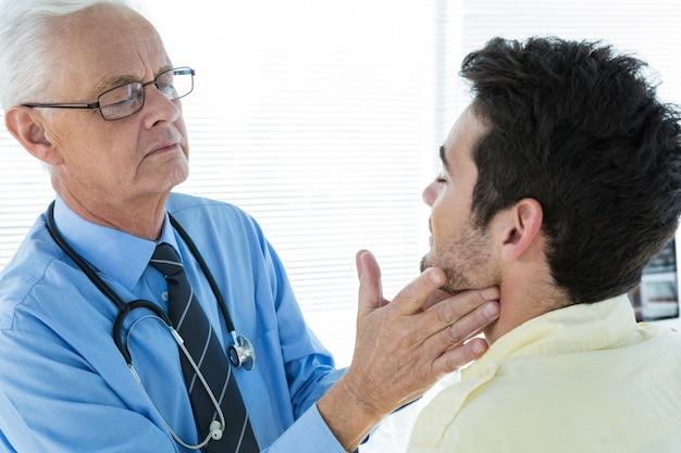 Doutor examinando a mandíbula do paciente