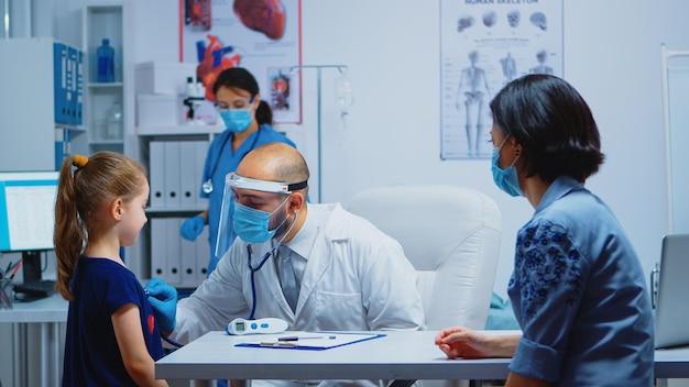 Doutor, examinando a menina pelo estetoscópio no consultório médico durante a pandemia. pediatra especialista em medicina com máscara prestando serviços de saúde, consulta, tratamento em gabinete hospitalar.