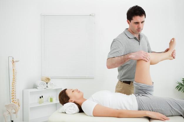 Doutor, examinando, a, perna, de, seu, paciente, enquanto, levantando, aquilo
