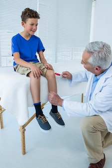 Doutor examinando o joelho do paciente