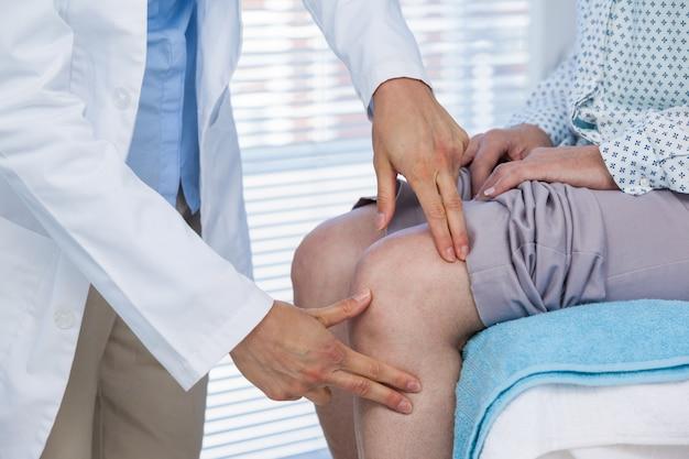 Doutor examinando paciente joelho