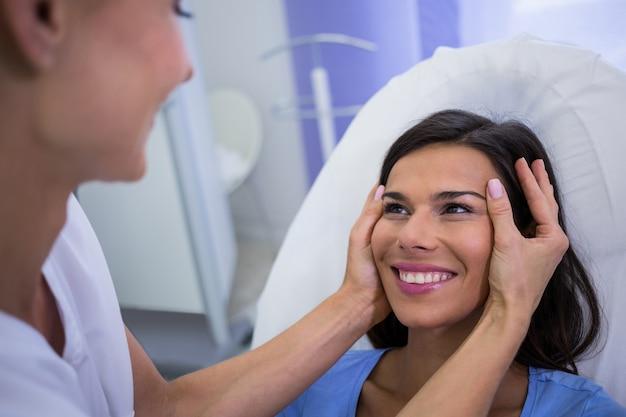 Doutor examinando pacientes do sexo feminino enfrenta na clínica