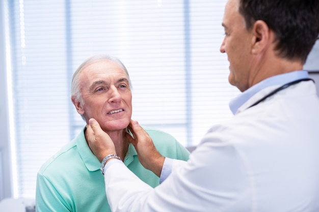 Doutor examinando pacientes idosos pescoço