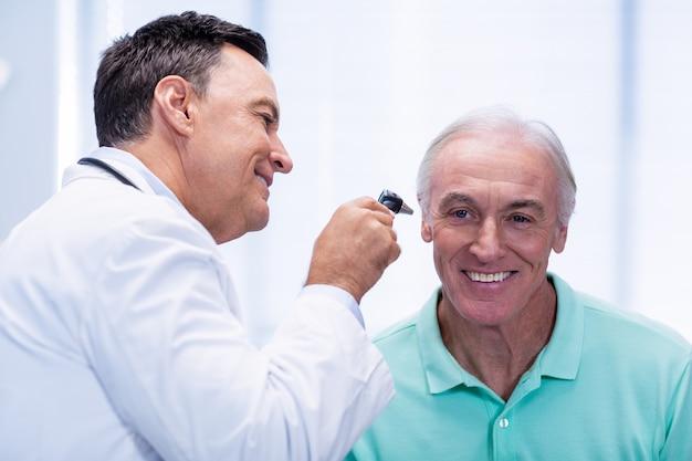 Doutor examinando pacientes ouvido com otoscópio
