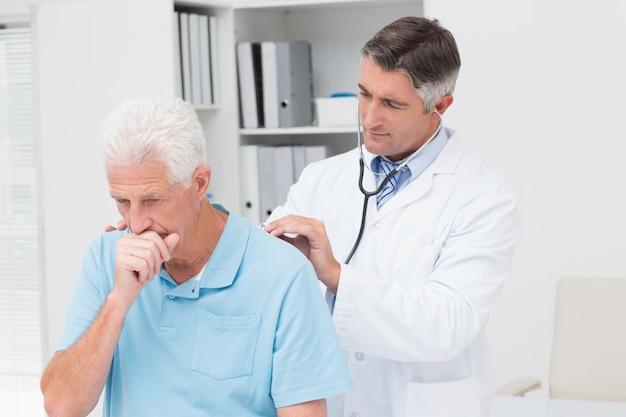 Doutor, examinando, tossir paciente sênior