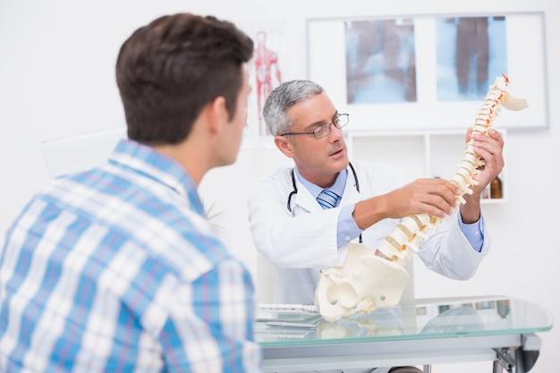 Doutor explica a coluna anatômica ao paciente