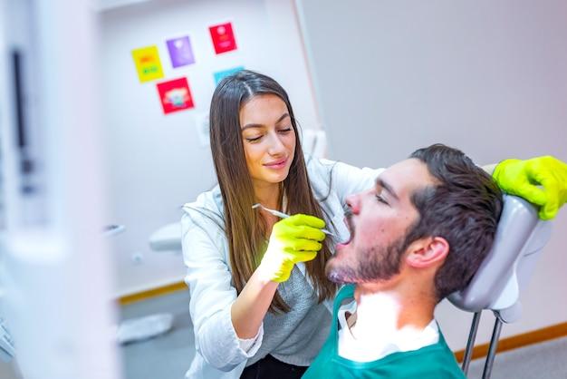 Doutor fazendo tratamento odontológico nos dentes do homem na cadeira de dentista.