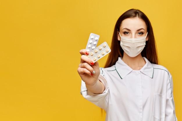 Doutor fêmea na máscara médica uniforme e protetora que guarda comprimidos em sua mão e que levanta no fundo amarelo, espaço da cópia, isolado. conceito de saúde