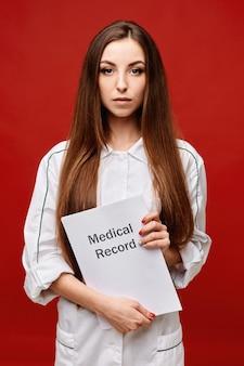 Doutor fêmea novo no uniforme médico que guarda um informe médico em suas mãos, espaço da cópia, isolado. conceito de saúde