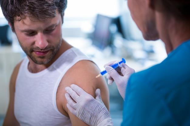 Doutor fêmea que dá uma injeção a um paciente