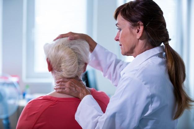 Doutor fêmea que examina um paciente